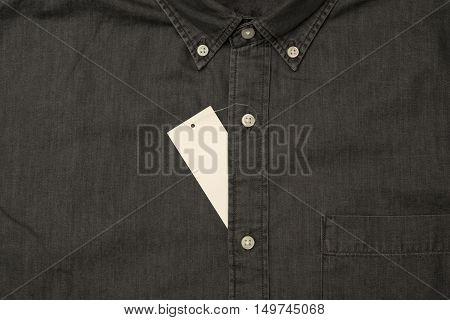 Black denim clothes with empty label. Closeup.