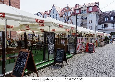 KOLOBRZEG POLAND - JUNE 23 2016: Temporary cafes and restaurants covered with a square umbrellas open for the summer season are located on the square in front of town hall