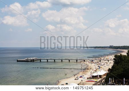 KOLOBRZEG POLAND - JUNE 22 2016: Unidentified sunbathers enjoying the sun on one of the widest sandy beach on the Polish coast of the Baltic Sea.