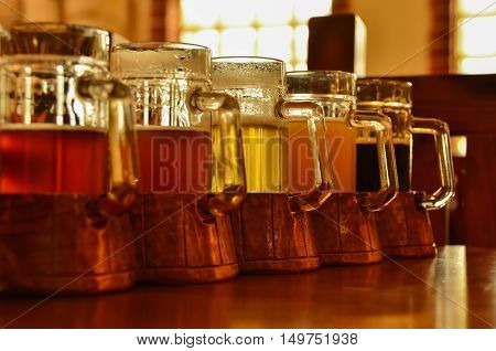 Five glasses different taste of beer stand in a row on the bar table. Shallow D.O.F.