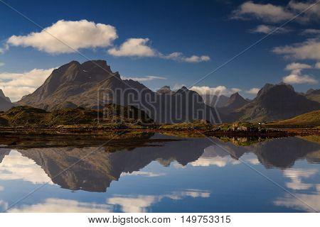 Mountain range of Moskenes refelcting in a fjord Lofoten Norway