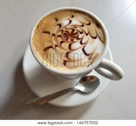 Delicious cappuccino cup with cream froth and chocolate design