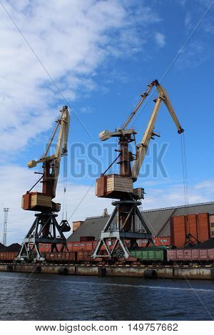 Two yellow cargo container cranes in harbor