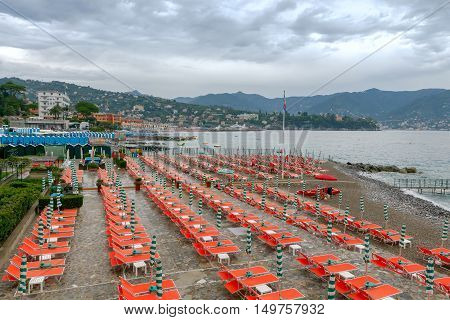 Beach chaise lounges and umbrellas on the beach in Saint Margherita Ligure. Italy. Cinque Terre.