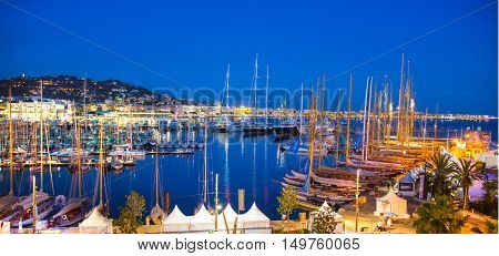 CANNES, FRANCE - 19 SEPTEMBER, 2016:   Old Port Vieux Port in the city of Cannes at night. Lots of sailing boats and power yachts anchored during the Sailing regatta.