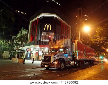 HONOLULU - JANUARY 8: Truck Delivers food to McDonalds Store in Downtown Honolulu Hawaii at Night McDonald's primarily sells hamburgers cheeseburgers chicken french fries breakfast items soft drinks milkshakes desserts. on January 8 2016 Honolulu Hawaii.