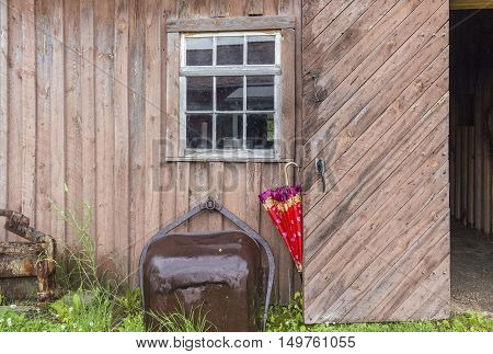 horizontal image of an old brown exterior wood slat wall with a small window with a red umbrella hanging on the door knob and an old iron rusted bucket leaning on the wall.