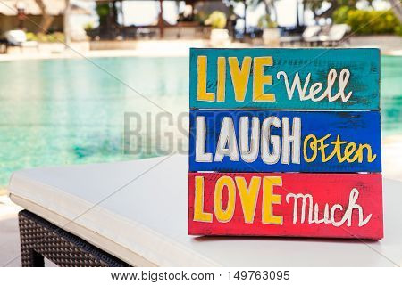 Inspirational Motivational Life Quote wooden board Live well Laugh often Love much on summer, tropical swimming pool background Copy space