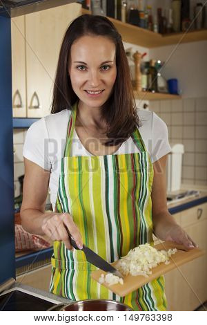woman in an apron cooking in the kitchen