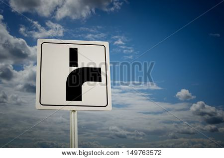 Road sign with cloudy sky background. Main road bends to the right.