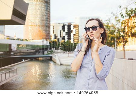 Woman is standing near modern buildings and pond while having mobile phone conversation discussing work tasks. Pretty girl walking in the street and talking on the phone. Ordering taxi by phone