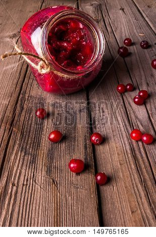 Fresh cranberries and cranberry jam or sauce on a rustic table