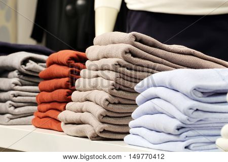 Clothes in stack in the shop. Clothes store