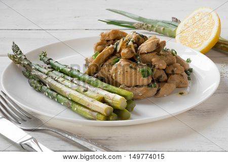 Asparagus with chicken in a sauce on a white plate