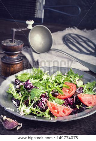 Fresh beet and cheese salad with tomatoes on plate rustic style. Toned