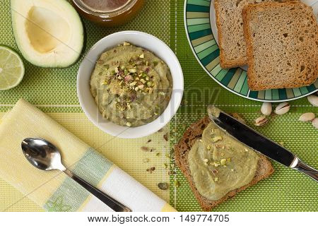 Mousse of avocado spread on toast and sprinkled with pistachios