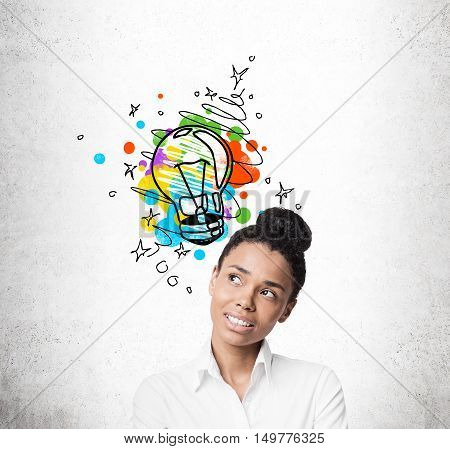 Close up of African American girl thinking. Colorful light bulb sketch is drawn on concrete wall behind her. Concept of good idea