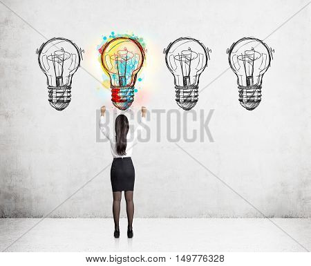 Rear view of business lady standing with hands in the air near concrete wall with light bulb sketches. Concept of looking for a good idea in business.