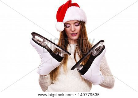 Winter skate sport people concept. Girl with santa claus cap. Young woman has white outfit and long beutiful hair female holdingtwo ice skates.