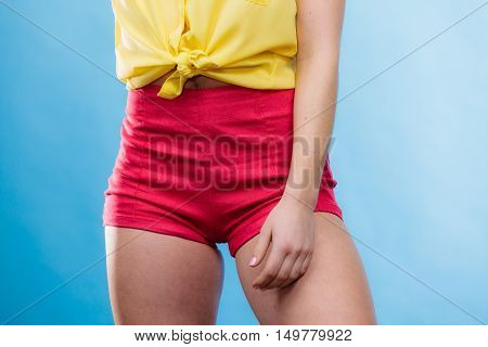 Closeup of alluring woman hips. Slim girl wearing yellow shirt and red shorts on blue. Summer fashion.