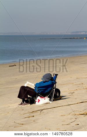 senior person that cant be recognized is resting on the beach during sunny winter day