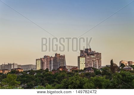 Neighborhood of low-rise residential buildings with multi-storey buildings on a steep slope. Evening skyline. City Belgorod Russia.