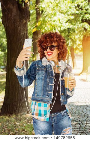 Happy millennial teenage girl in denim jeans and denim jacket taking a selfie in park in autumn. Cool curly redhead young woman with takeaway coffee and sunglasses photographing herself in fall.