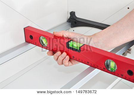 Assembling kitchen furniture mounting shelf with dryer handyman measuring level.