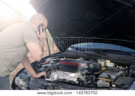 Close up of a broken down car engine open and smoking in a rural area and the driver looking at the engine