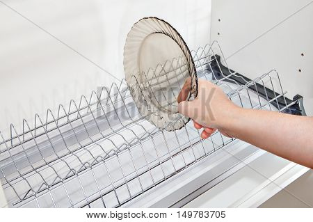 Close-up housewives hand takes a plate from the wall kitchen cabinet with wire dish drainer inside.