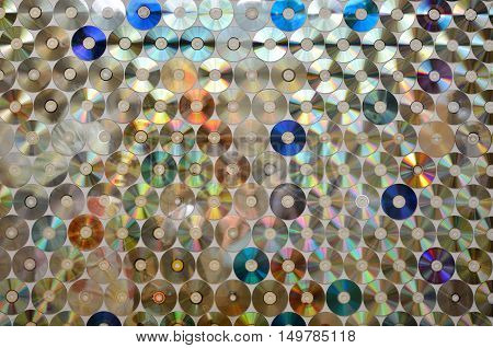 Background on the wall with old damaged discs cd.