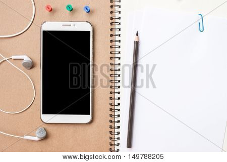 smart phone on notebook / Blank screen Smartphone on notebook, wooden table in perspace