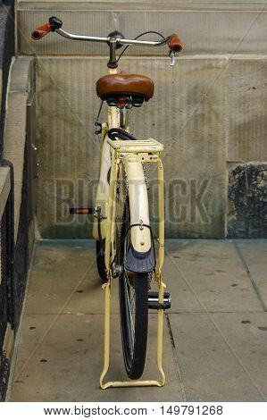 A old yellow bicycle. leather seat with shock absorbers and wheel
