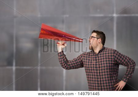 Hipster man shout in trumpet . Mixed media