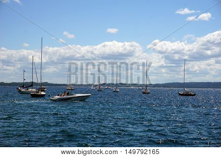 HARBOR SPRINGS, MICHIGAN / UNITED STATES - AUGUST 1, 2016: A motorboat moves past sailboats moored it the Harbor Springs Yacht Basin.