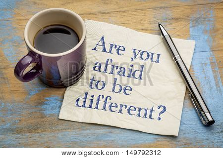 Are you afraid to be different question - handwriting on a napkin with a cup of coffee