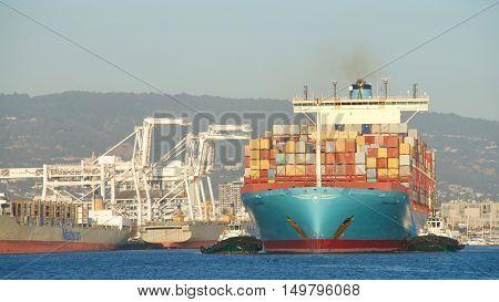 Oakland CA - September 29 2016: Cargo ship GERNER MARSK with multiple tugboats assisting the vessel to maneuver out of the Port of Oakland.