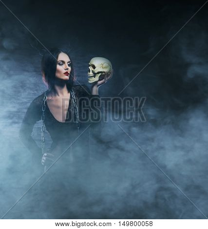 Halloween concept: young and sexy witch makes the witchcraft in the dungeon