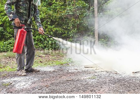 A man demonstrating how to use a fire extinguisher