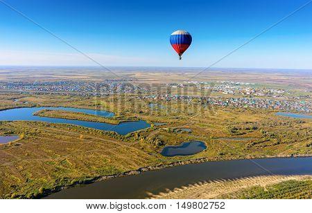 Kaskara, Russia - October 1, 2016: Hot air balloon flying over river landscape at autumn day. Kaskara at background. Tyumen region
