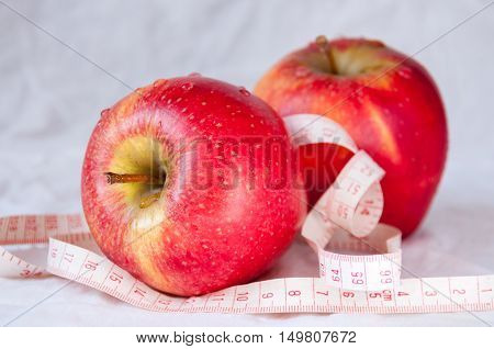 Two red apples among white tape measures