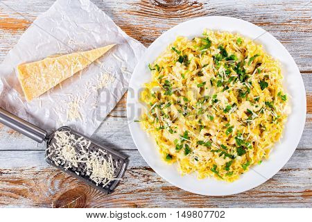 Fettuccine Alfredo served in a sauce of cream butter and grated Parmesan cheese sprinkled with parsley. piece of parmesan cheese on parchment paper on old peeling paint planks view from above