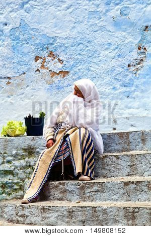 CHEFCHAOUEN, MOROCCO - JANUARY 2, 2014: Muslim woman resting on the steps after shopping in the souk.