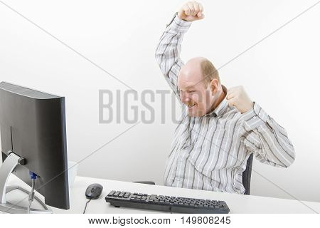 Successful businessman cheering while looking at computer on desk in office