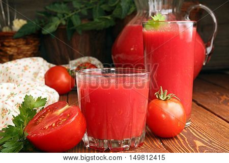 Two glasses jug of tomato juice and fresh tomatoes on wooden table
