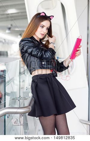 Girl model wearing cat ears holding pink tablet and listen music. Indoor young female portrait wearing leather jacket and black skirt. Fashion lady with long brown hair wear cool outfit and high heels