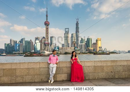 Shanghai China - October 26 2013: Chinese couple at the Bund. It is a waterfront area central Shanghai which runs along the western bank of Huangpu River facing Pudong skyscrapers Shanghai China