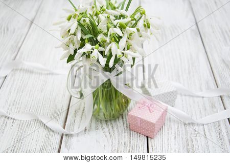 Beautiful snowdrops in a vase with gift box on a wooden background
