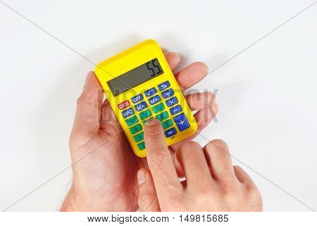 Hands calculate using a digital calculator on a white background