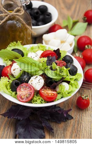 Salad with mozzarella tomatoes basil and olives on a wooden table